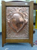AN INTERESTING ARTS AND CRAFTS COPPER REPOUSSE PANEL WITH ARMORIAL CREST AND IN OAK FRAME. 48 x
