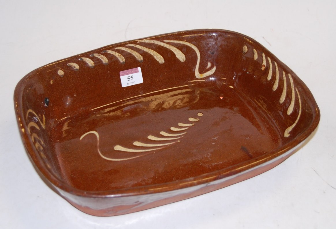 Lot 55 - An early 20th century slip glazed pottery oven dish, w.