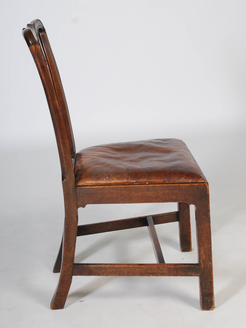 Lot 45 - A set of four George III mahogany dining chairs, the shaped top rails above pierced scrolling and