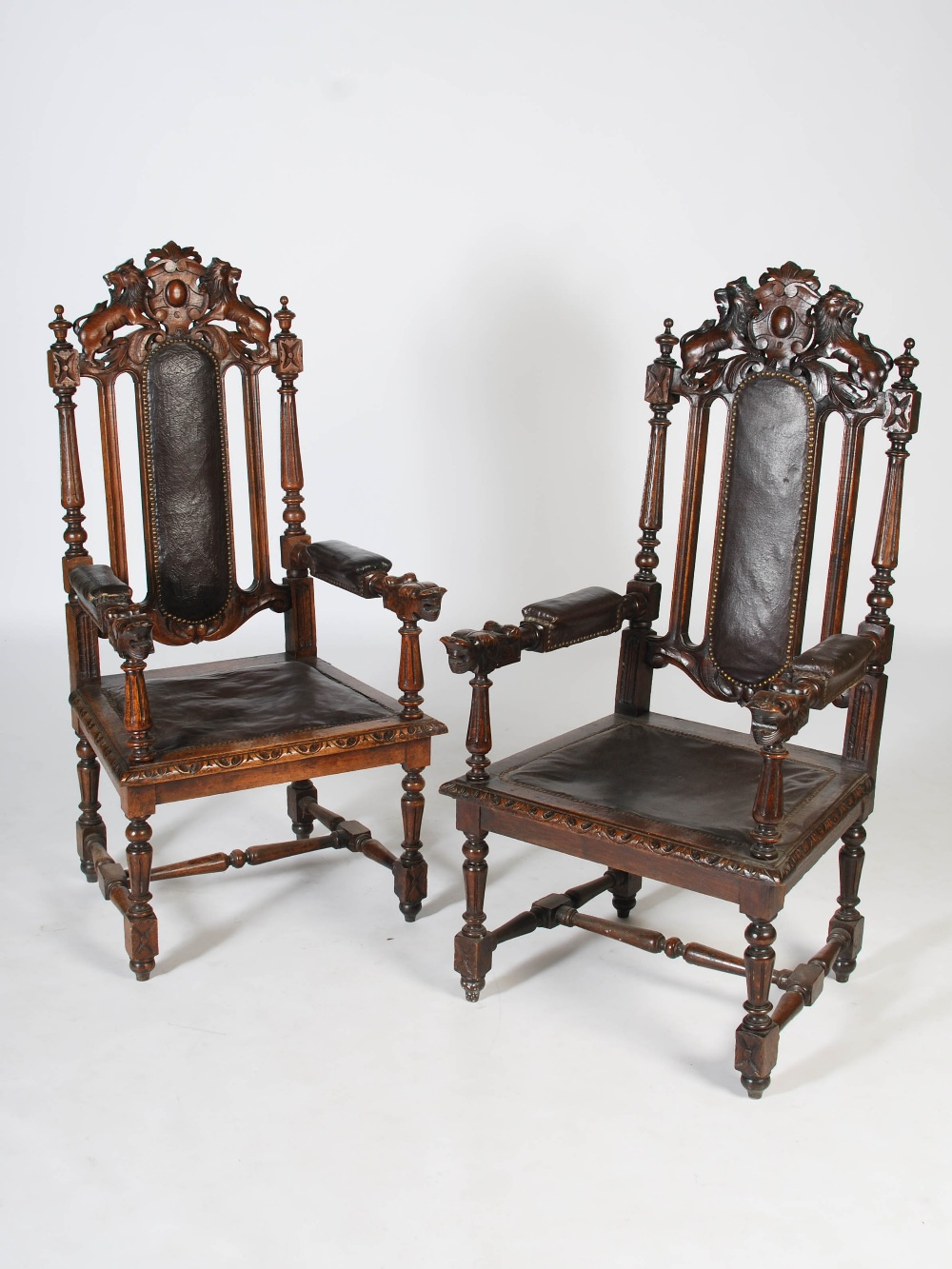 Lot 80 - A pair of late Victorian oak armchairs, the top rails carved with shields flanked by lions above