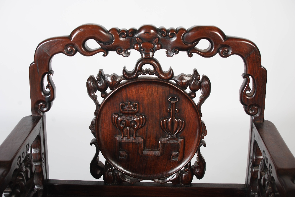 Lot 108 - A Chinese dark wood armchair, Qing Dynasty, the scroll carved top rail centred with a bat above a