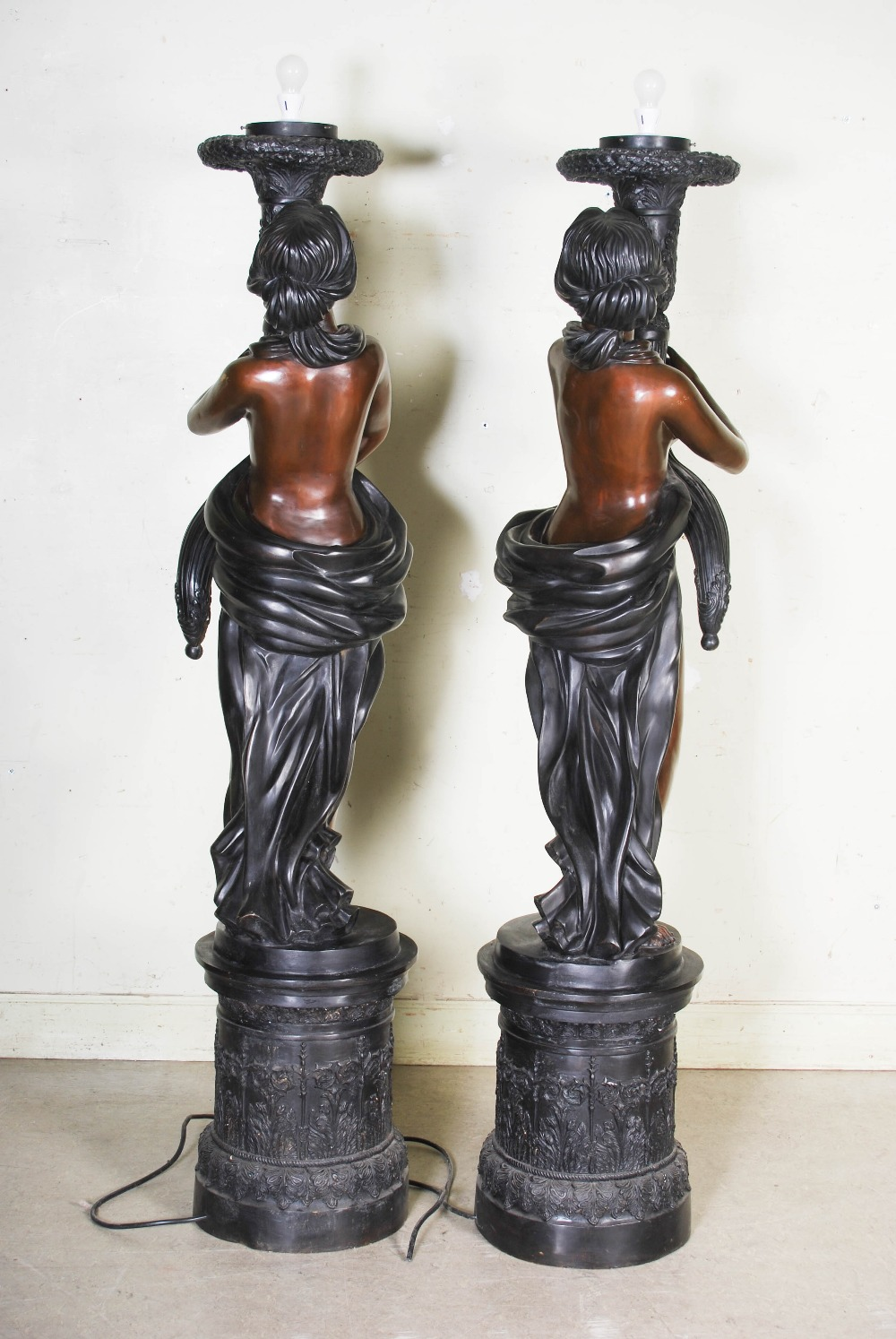 Lot 99 - A pair of decorative 20th century bronze figural torcheres, cast with semi clad maidens holding