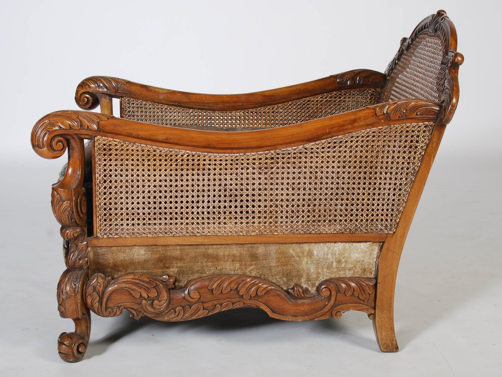 Lot 56 - An Edwardian walnut three piece Bergere suite, comprising; three seat sofa and two armchairs, with