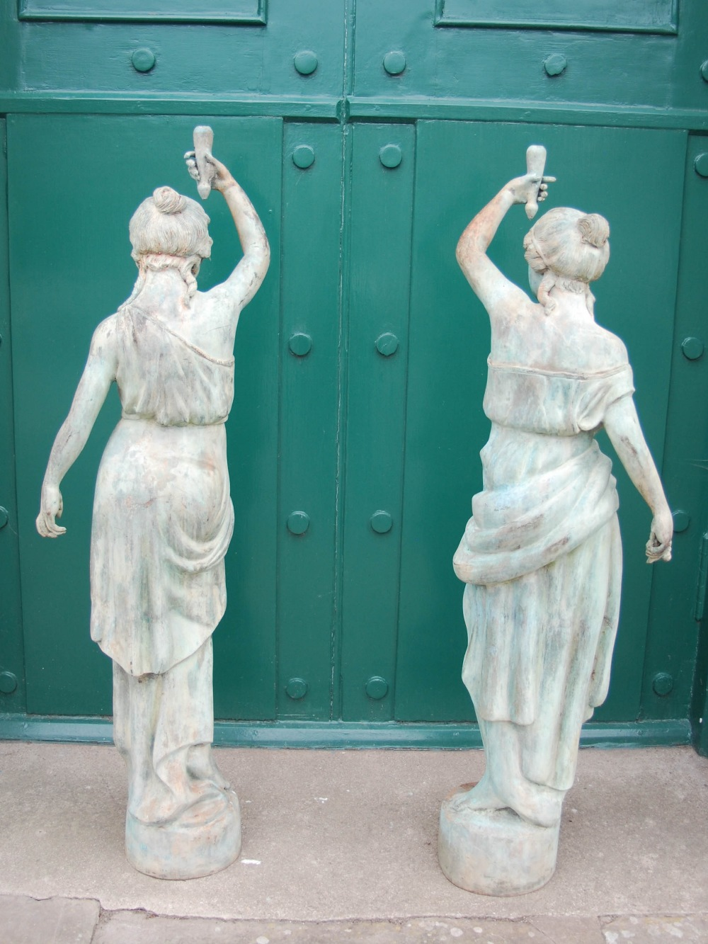 Lot 75 - A pair of 20th century bronze figural torcheres, modelled as classical maidens holding aloft foliate