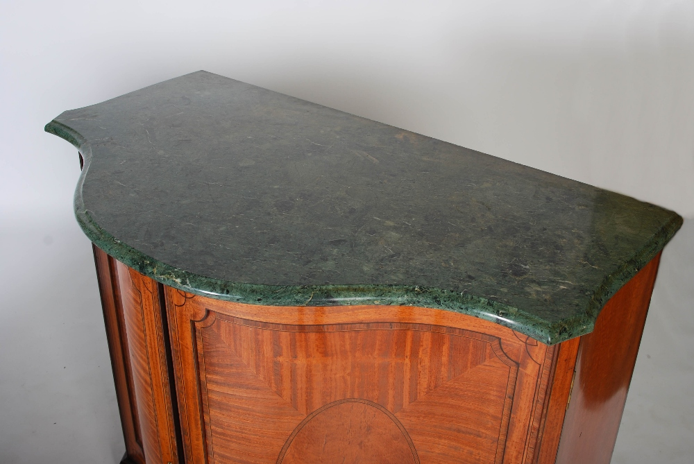 Lot 31 - A pair of early 20th century satinwood serpentine side cabinets, the green and white marble tops