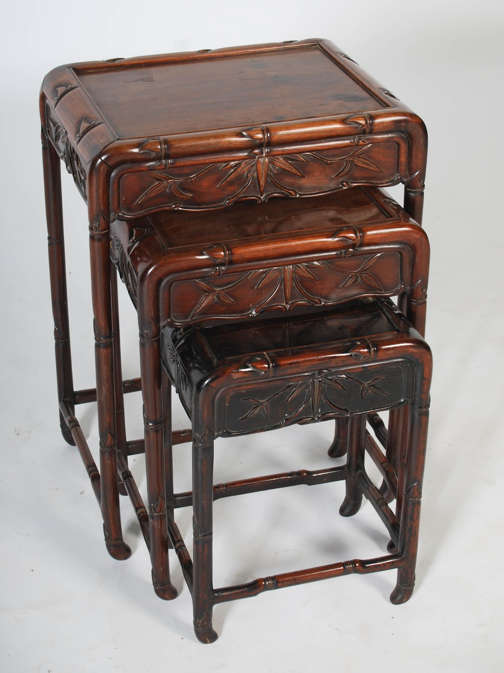 Lot 50 - A nest of three Chinese dark wood occasional tables, Qing Dynasty, the rectangular panelled tops