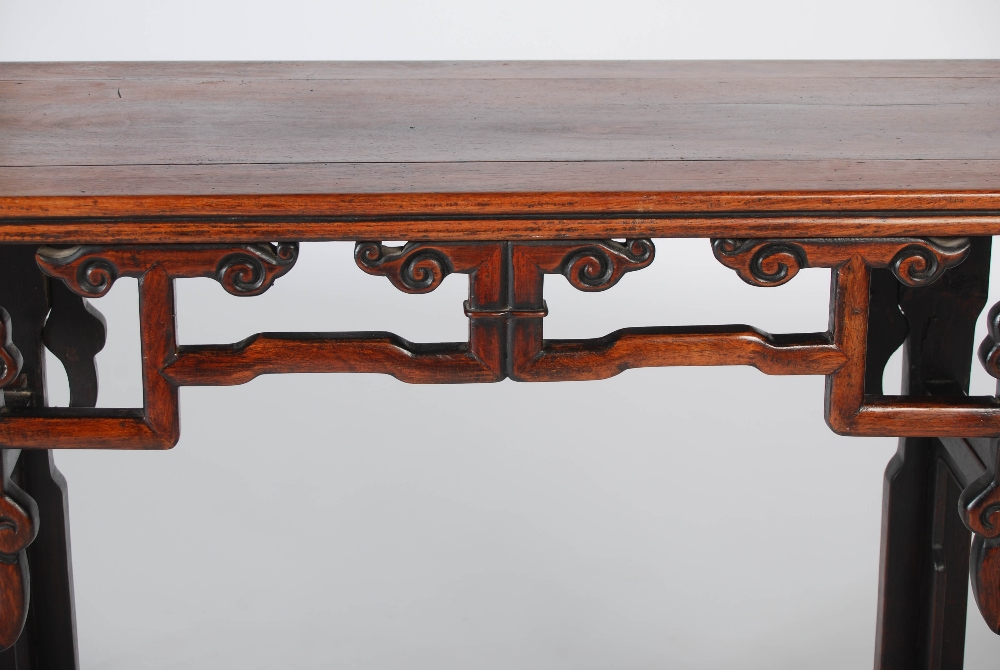 Lot 65 - A Chinese dark wood altar table, Qing Dynasty, the rectangular panelled top with convex ends above a