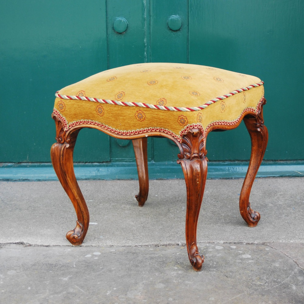 Lot 24 - A Victorian walnut square shaped dressing table stool, the serpentine upholstered seat raised on