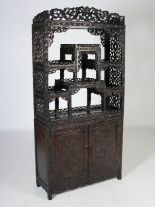 Lot 41 - A Chinese dark wood display cabinet, Qing Dynasty, the upper section with six open shelves within