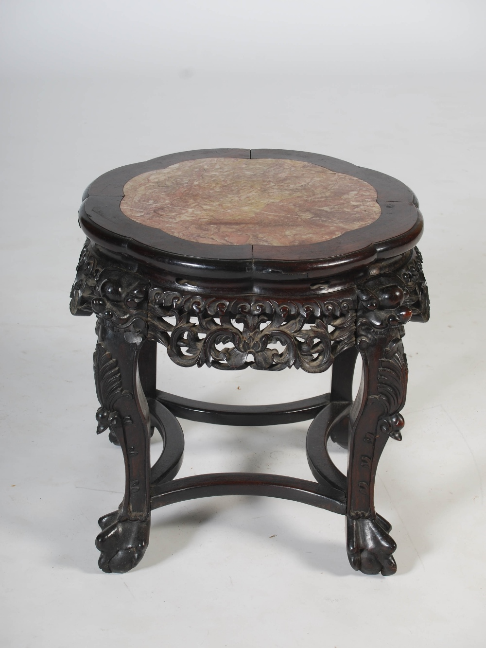 Lot 58 - A Chinese dark wood jardiniere stand, Qing Dynasty, the shaped circular top with mottled red