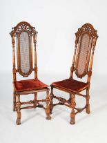 Lot 36 - A pair of late 19th/early 20th century Continental walnut hall chairs, the upright backs with
