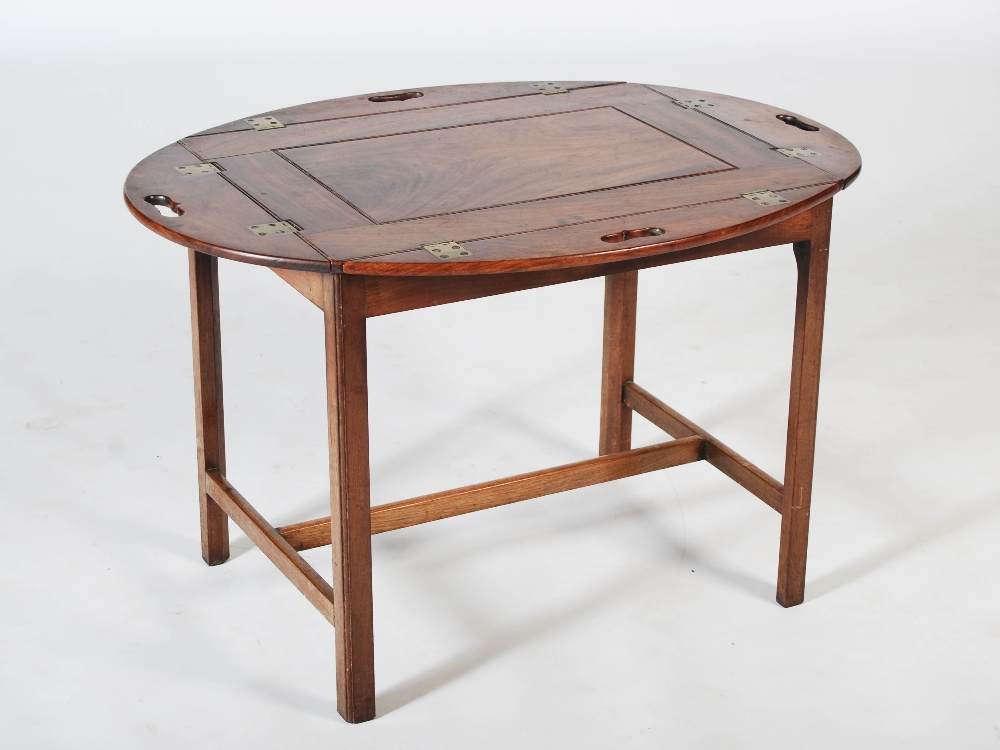 Lot 34 - A 19th century mahogany butlers tray on associated stand, the oval shaped tray with hinged gallery