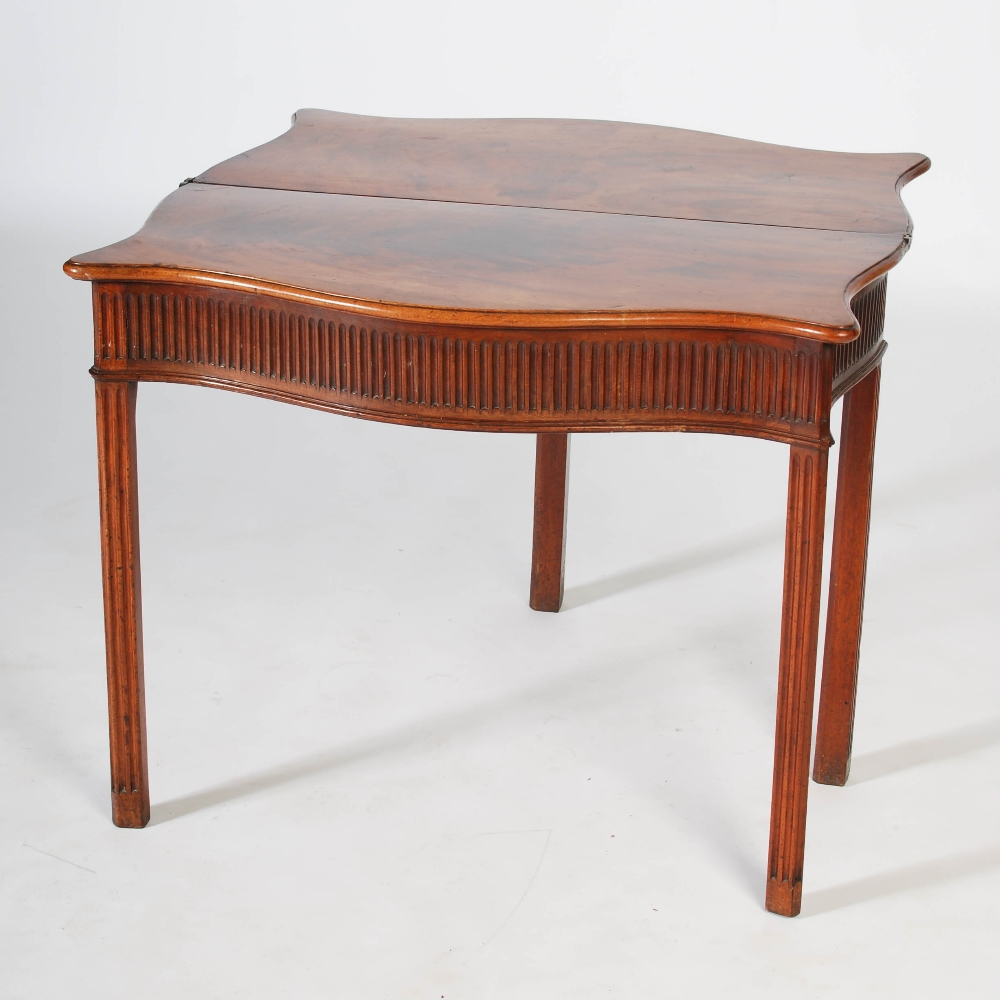 Lot 103 - A George III mahogany serpentine tea table, the shaped and hinged top above an arcaded frieze,