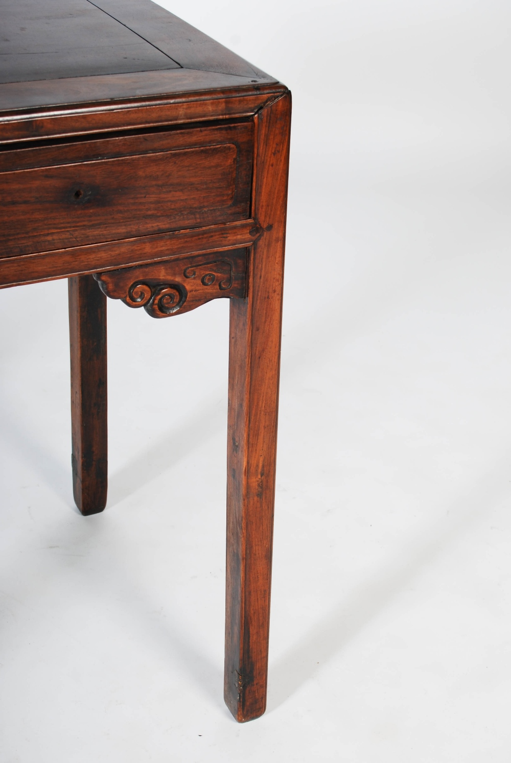 Lot 70 - A Chinese dark wood table, Qing Dynasty, the rectangular panelled top of two frieze drawers,