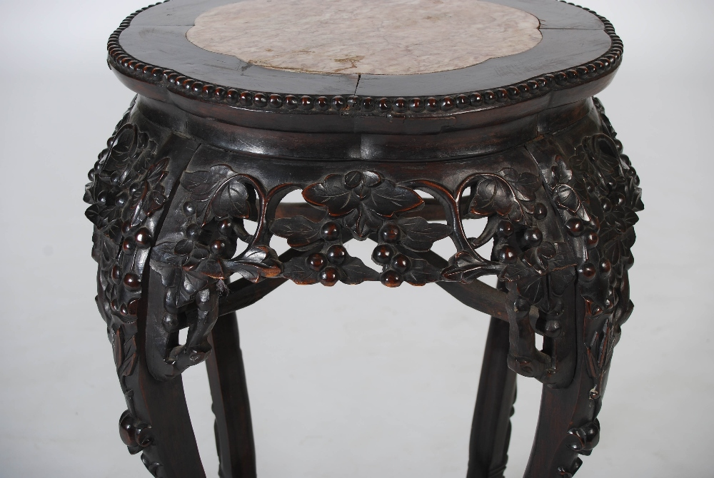 Lot 48 - A Chinese dark wood jardiniere stand, Qing Dynasty, the shaped circular top with a mottled red