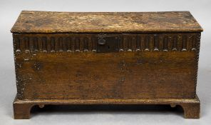 A 17th/18th century oak plank coffer The front panel with short gadrooned decoration,
