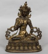 A Sino-Tibetan gilt bronze figure of a deity Modelled seated on a lappet cast plinth base. 21.