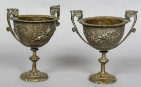 A pair of 19th century silvered bronze pedestal urns Each with twin mask headed handles,