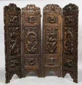 An Eastern carved wood four fold screen Each panel worked in deep relief with mythical beasts