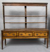 A George III oak dresser The open rack above three crossbanded drawers with brass handles above