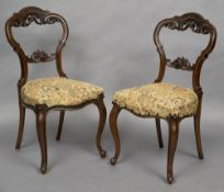 A pair of Victorian walnut dining chairs The pierced scroll carved backs above the overstuffed seat,