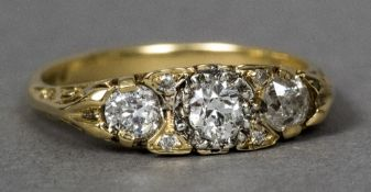 An Edwardian 18 ct gold three stone ring Of navette form above pierced scrolling shoulders. 1.