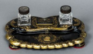 A 19th century papier mache inkstand Mounted with two carved hardwood topped glass inkwells and