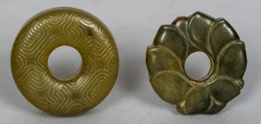 A Chinese carved jade roundel Worked as a lotus flower; together with another geometrically carved.