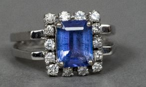 A 14 ct white gold diamond and tanzanite ring The central claw set tanzanite surrounded by a border