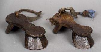 A pair of antique carved wooden Indo-Portuguese stilted shoes Of typical form with rope and leather