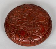 A Chinese red lacquer box and cover Of circular section and worked with floral sprays.