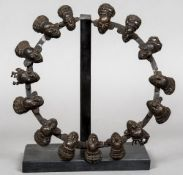 The Titcar Tribe of Cameroon, a ring of patinated bronze figural masks Approximately 32 cm diameter.