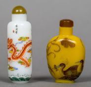 Two Chinese decorated glass snuff bottles and stoppers One worked with a dragon,