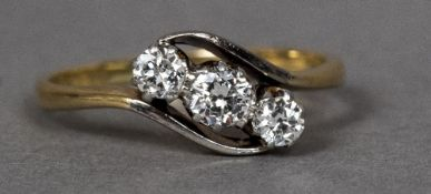 An 18 ct gold diamond three stone crossover ring CONDITION REPORTS: Generally in