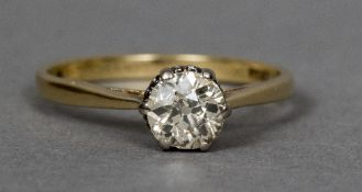 An 18 ct gold and platinum diamond solitaire ring The claw set stone approximately 0.65 carat.