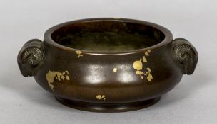 A Chinese bronze twin handled censor The handles modelled as rams heads, the body gilt splashed,