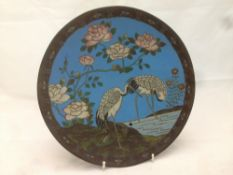 A 19th century Japanese cloisonne plate Typically decorated with cranes in a river landscape within