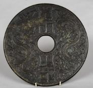 A large Chinese carved green and russet jade bi disc Carved with dragons flanking calligraphic text.
