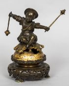 A bronze cast table bell Modelled as an Eastern child striking a bell upon which he is seated,