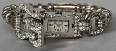 A platinum cased diamond set lady's concealed dial Rolex wristwatch The signed rectangular dial