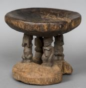 An African carved wooden tribal stool The dished seat supported by four figural columns above a