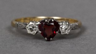 An Edwardian 18 ct gold and platinum diamond and ruby ring The central heart shaped diamond flanked