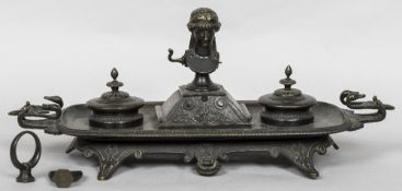 A large 19th century patinated bronze desk stand The main body with twin swan mask handles,