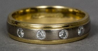 An 18 ct two-tone gold and diamond ring Of band form set with four gypsy set diamonds.