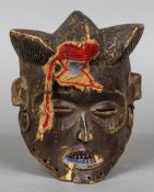 An African carved wooden tribal mask Modelled as a human face with section of applied headdress and