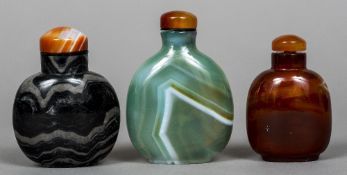 Three Chinese carved hardstone snuff bottles and stoppers Of typical form. The largest 8 cm high.