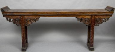 A 19th century Chinese altar table The panelled rectangular top above the carved pierced spandrels,