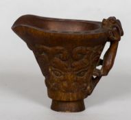 A Chinese horn libation cup Of typical form, the handle worked as a mythical beast,