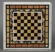 A late 19th/early 20th century specimen marble table top Inset with chess and cribbage boards. 35.