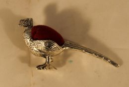 A small pin cushion in the form of a pheasant